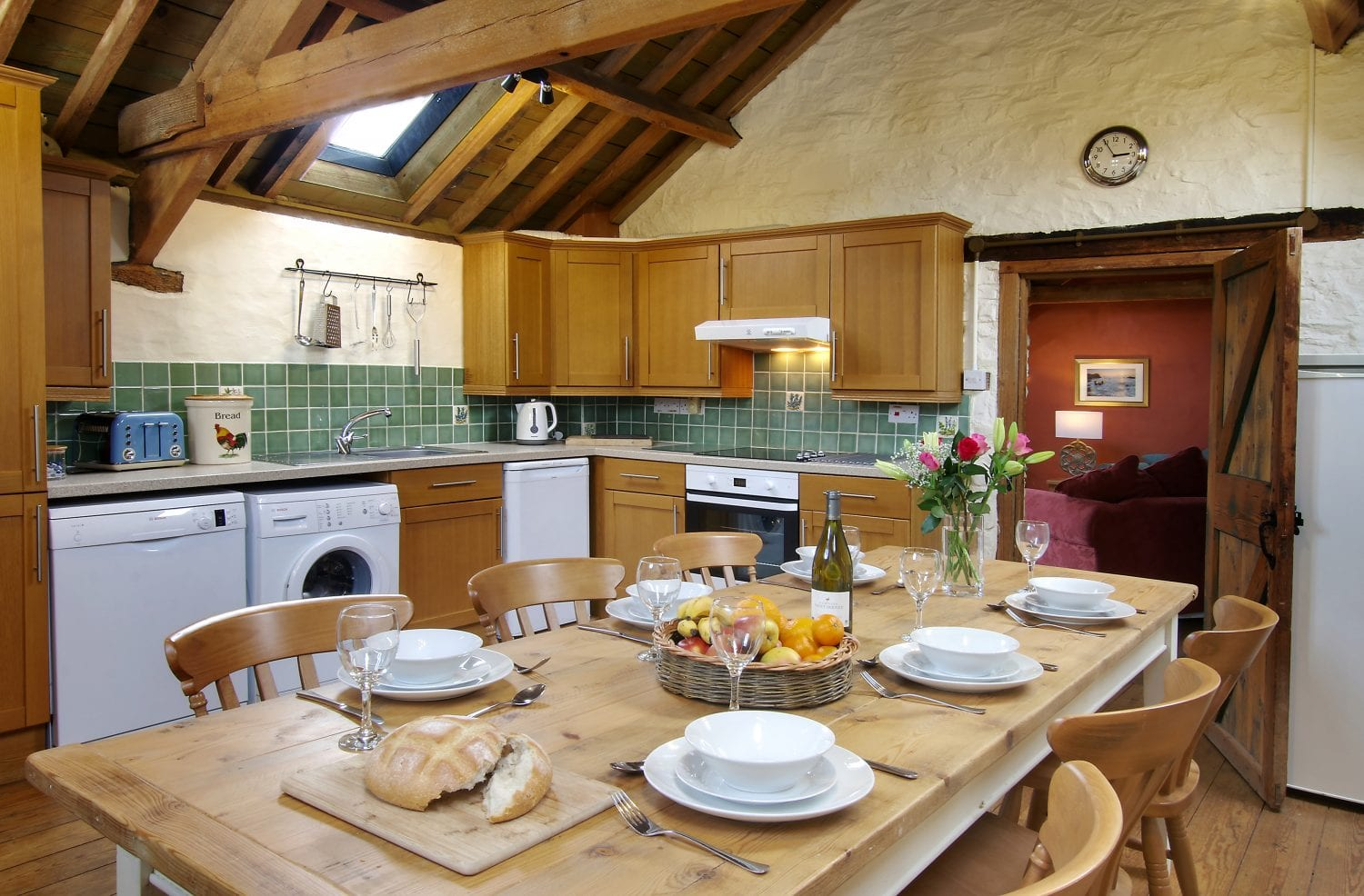 The kitchen in Mill House with teh large farmhouse table set for dinner